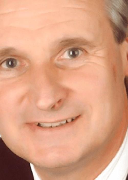 Porträt von Mann mit grauen Haaren und schwarzem Jackett, Dr. Manfred Lind, Triple-A AG, Business
