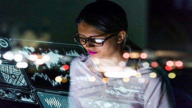 Frau mit dunklen Haaren, Brille, lila Lippenstift schaut auf mehrere Bildschirme, Smart Company, United Smart Cities, Triple-A AG