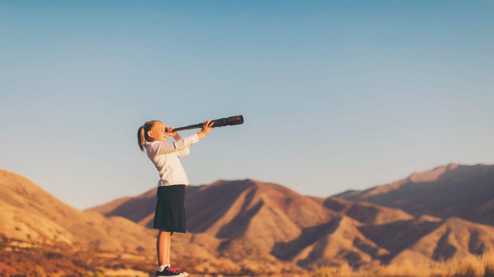 Mädchen mit weißer Bluse und schwarzem Rock blickt mit Fernrohr über Wüste und Berge - Triple-A AG