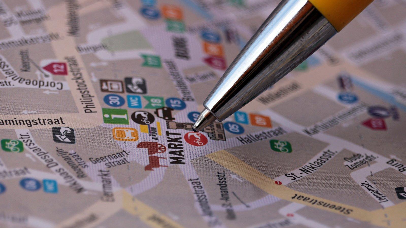 Kugelschreiber zeigt auf Stadtkarte, Brügge, Smart City, United Smart Cities, Triple-A AG